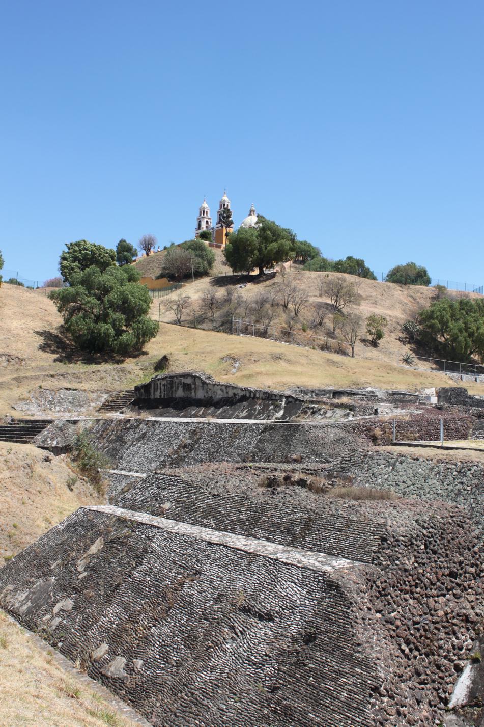 Dieser dahinter liegende Erdhügel mit der Kirche auf der Spitze, ist die größte Pyramide der Welt.
