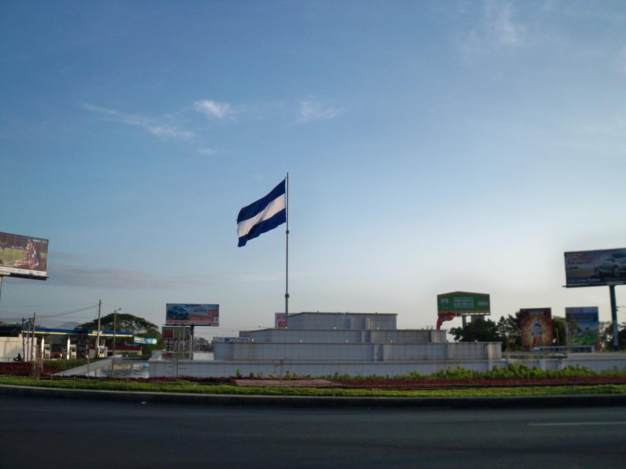 Kreisverkehr in Managua. Voraus ist die Fahne von Nicaragua.