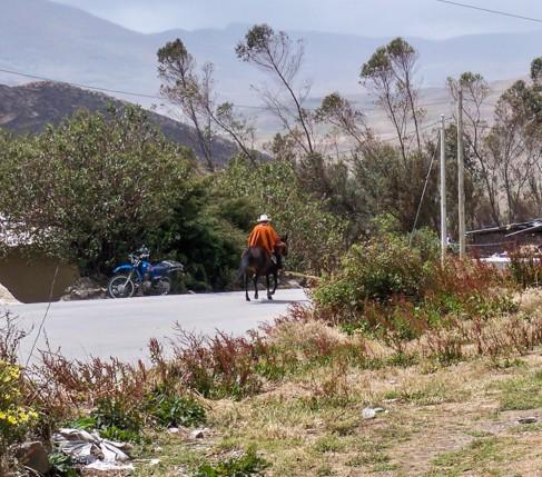 Cowboy mit Poncho reitet durch das Dorf.